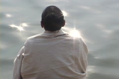 Stock Video Footage of A contemplative Hindu pilgrim at a sparkling river.