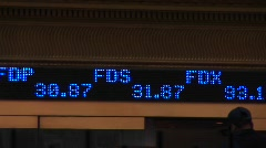 An abbreviated ticker-tape shows stock symbols and their current Stock Footage