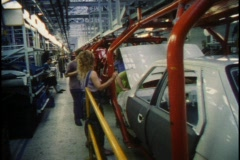 Men and women work together on an auto assembly line. Stock Footage