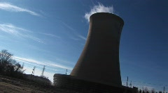 Steam rises from the top of a nuclear power plant in this tilted Stock Footage
