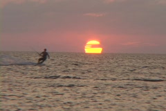 A windsurfer surfs across the water in silhouette against the sun. Stock Footage