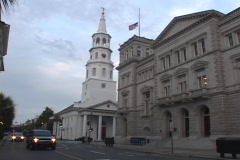 Cars drive by a white church with a tall steeple and a government building. - stock footage