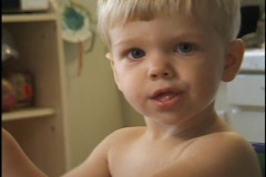 A young toddler stretches to look around the camera while eating. Stock Footage