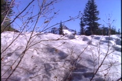 A snow-covered mountain appears beyond a snowbank. Stock Footage