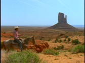 Stock Video Footage of People ride horses through Monument Valley.