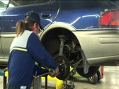 A mechanic pulls repeatedly on a wheel's axle Stock Footage