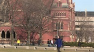Stock Video Footage of Students walk across campus as the camera pans up one of Harvard's