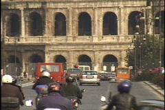 Traffic travels down a street in front of the Coliseum. Stock Footage