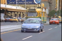 Cars pass a tram while traveling down a busy downtown street in Melbourne, Stock Footage
