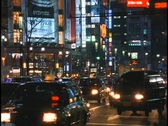 Stock Video Footage of Heavy traffic drives down a street in the Ginza district of Tokyo, Japan.