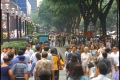 Crowds of people walk down a sidewalk in the Orchard Road district of Singapore. Stock Footage