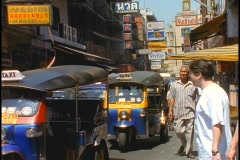 Pedestrians walk past Tuk-tuk taxis idling on a street in Bangkok, Thailand. Stock Footage