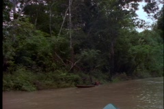 An Amazonian man canoes down the Amazon River in Brazil. Stock Footage