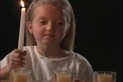 A young girl lights a candle. Stock Footage