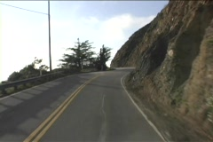 A narrow two lane road curves around mountains. Stock Footage