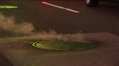 Medium-shot of steam rising from a manhole cover. Stock Footage