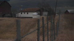 The camera looks over a fence to a rural farm in early winter Stock Footage
