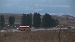 A yellow school bus travels along a rural road Stock Footage