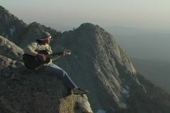 A man plays guitar on top of a mountain summit. Stock Footage