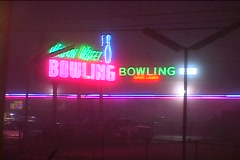 A neon sign is over the entrance to a bowling alley Stock Footage