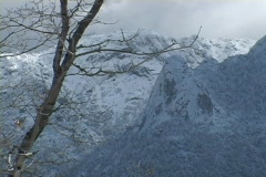 Dense clouds cover the peaks of snow covered mountains. Stock Footage