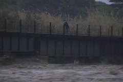 A man stands on a bridge above a flooded river. Stock Footage