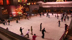 The camera shows skaters at night on the Rockefeller Center - stock footage