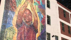 Camera pans up to reveal a colorful mural on an inner-city Stock Footage