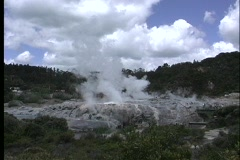 A geyser steams in a thermal region near Rotorua, New Zealand. - stock footage