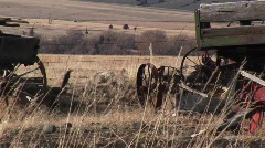 Broken and abandoned farm machinery rest in a field Stock Footage