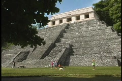 People walk and rest near a large, ancient MesoAmerican stone pyramid. Stock Footage