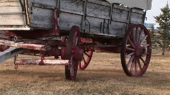 A covered wagon with its wagon wheels painted red Stock Footage