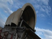 Stock Video Footage of Worms-eye view of a covered wagon against a blue sky