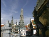 Stock Video Footage of Stone pagodas decorate the rooftops of the buildings of Bangkok, Thailand.