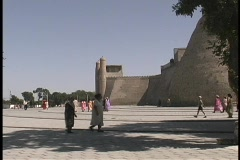 People walk outside The Ark of Emir's Palace in the ancient city of Bukhara, Stock Footage