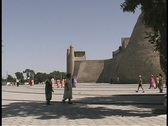 Stock Video Footage of People walk outside The Ark of Emir's Palace in the ancient city of Bukhara,