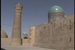 Birds fly around the ancient Kalyan Minaret and two turquoise mosque domes. Stock Footage