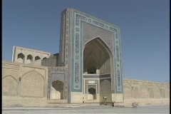 People walk in front of an ancient mosque in Bukhara, Uzbekistan. Stock Footage