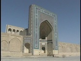 Stock Video Footage of People walk in front of an ancient mosque in Bukhara, Uzbekistan.