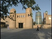 Stock Video Footage of People walk in front of the entrance to the walled city of Khiva, Uzbekistan.