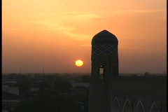 A mosque dome silhouettes the orange sky at golden-hour. Stock Footage