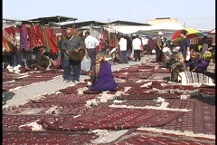 People browse the beautiful carpets for sale at the Tolkuchka Bazaar. Stock Footage