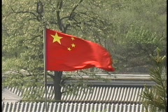 A Chinese flag flies over rooftops on a summer day. Stock Footage