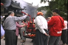 Men and women light candles outside the Big Goose Pagoda in Xian, China. Stock Footage