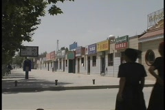 A group of people walk by a row of shops in Shache, China. Stock Footage
