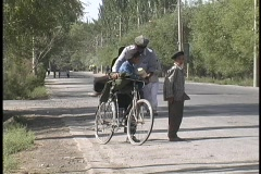 Muslim women in abayas walk by a man on a bicycle with two children. Stock Footage