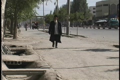 A man in traditional garb walks along a street near Kashgar, China. - stock footage