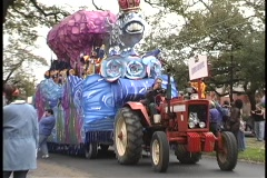 Costumed characters on a Mardi Gras float throw beads to the crowds along the Stock Footage