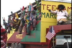 A group of very colorfully costumed men ride together on a Mardi Gras float and Stock Footage