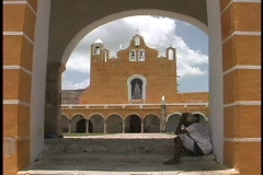 A terracotta colored church is seen across the courtyard of a convent in Izamal, Stock Footage